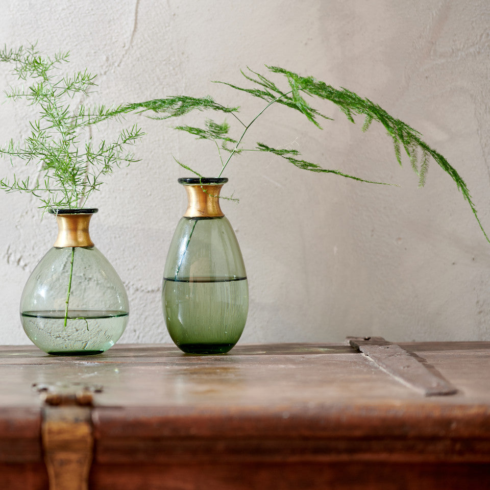 Miza Mini green glass vases with brass collar, styled on a wodden chest with fern foliage.
