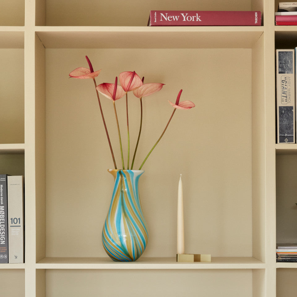 Multi yellow and blue coloured glass tulip vase containing tall-stemmed flowers, styled on a shelving unit with a candle in holder.
