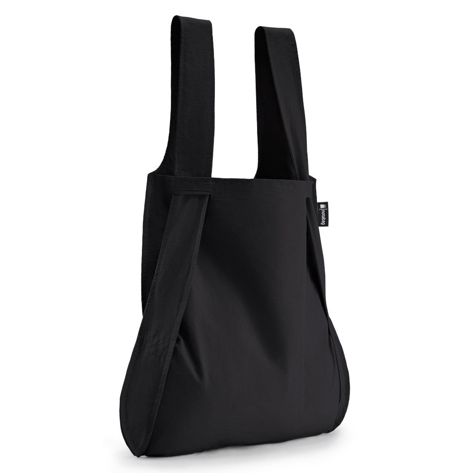 Not-a-bag re-usable fold-away pouch, black, shown as shopping bag.