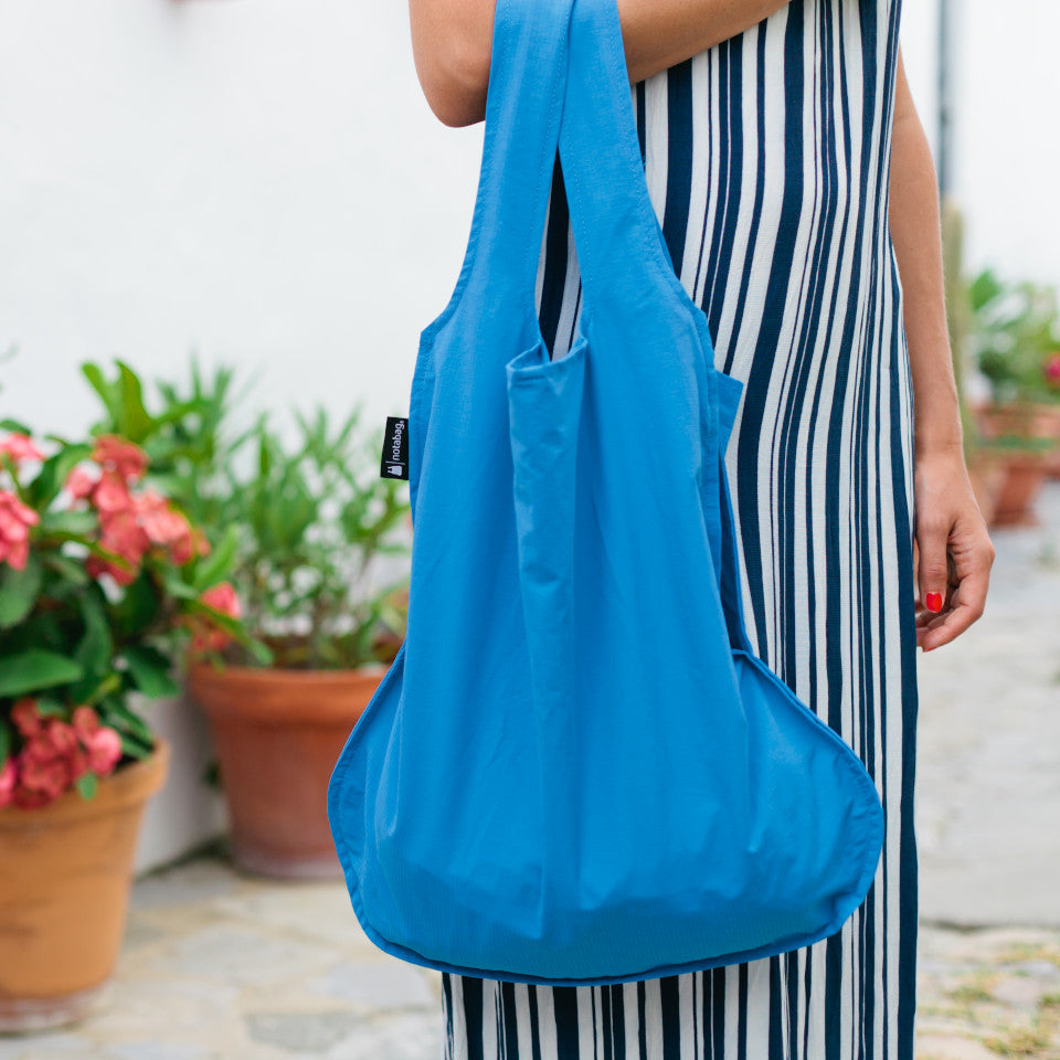 Not-a-bag re-usable fold-away pouch, blue, shown as shopping bag, styled.