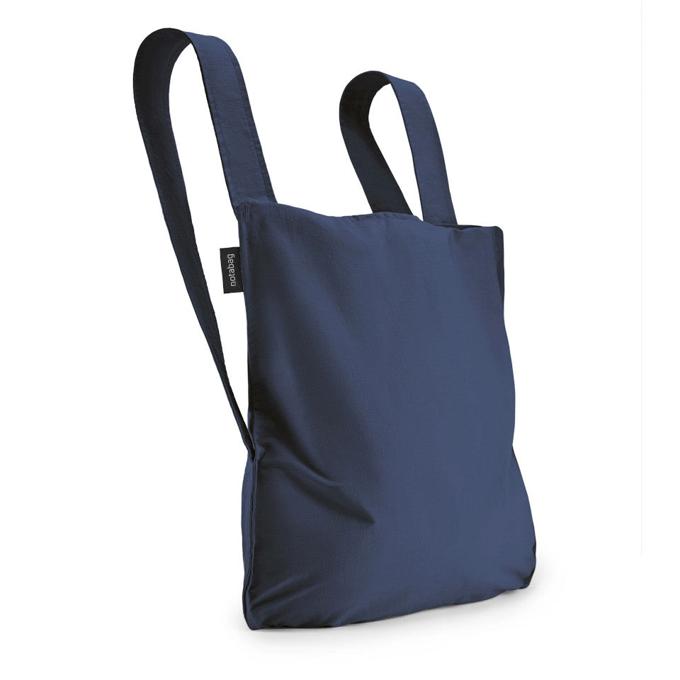 Not-a-bag re-usable fold-away pouch, navy blue, shown as backpack.