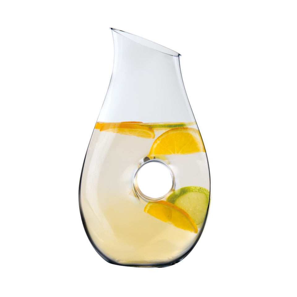 'O' mouth-blown glass pitcher filled with water and citrus slices.
