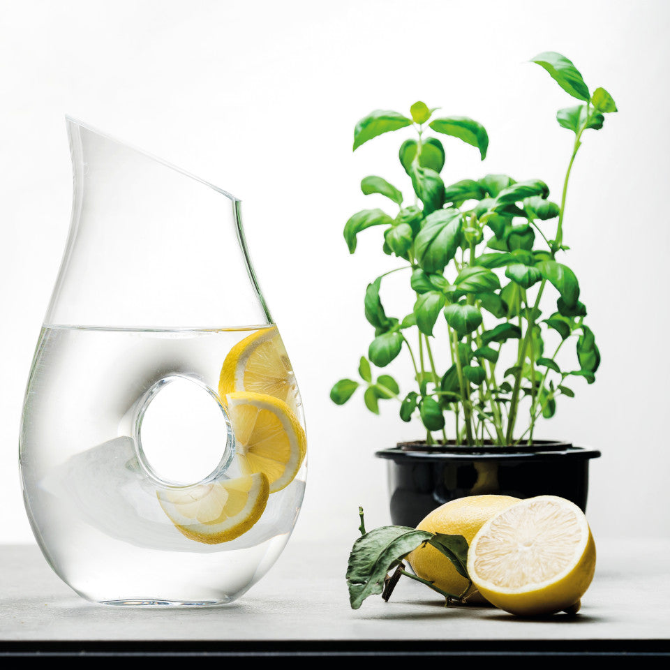 'O' mouth-blown glass pitcher filled with water and citrus slices and styled with a basil plant and fresh lemons.