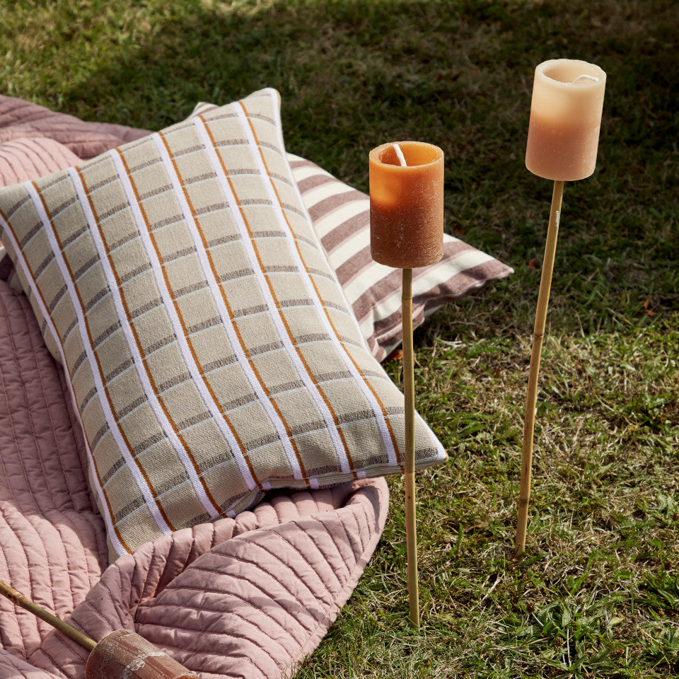 Outdoor torches, terracotta and wanut styled standing in a lawn with cushions and a throw.
