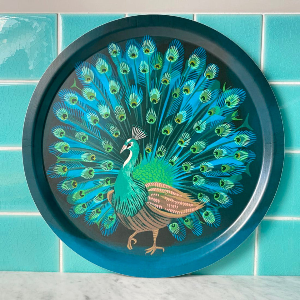 Peacock by Asta Barrington, peacock in full tail-feather on indigo background, 39cm round tray, styled leaning against a turquoise tiled wall.