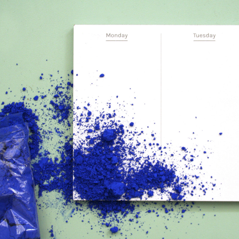 Plan Your Week desk planner detail, styled with blue paint powder (spilled).