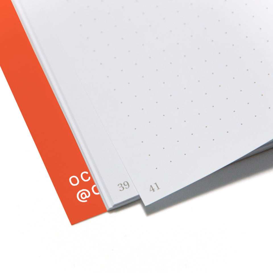 PRIVATE orange notebook with white lettering, detail of page corners.