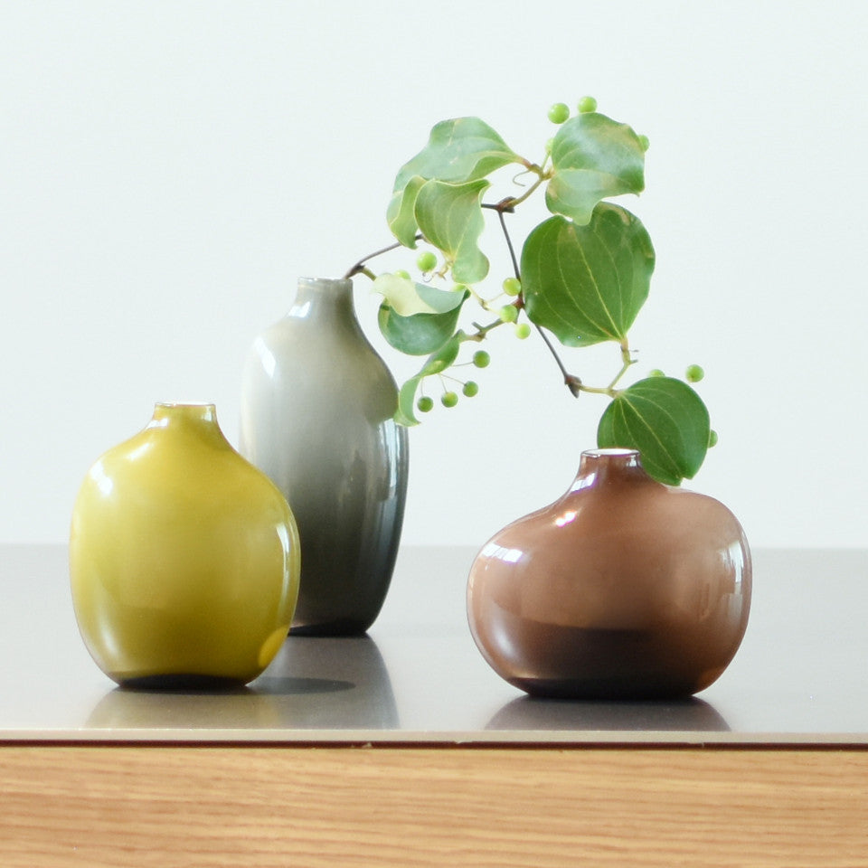Sacco r-l, brown glass small vase, large grey glass and medium green glass vases, styled with foliage.