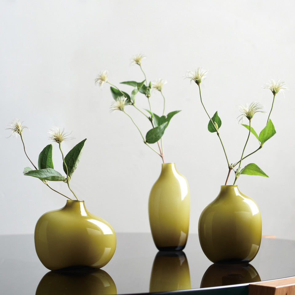 Sacco green glass l-r small, large and medium vases styled with flowers.