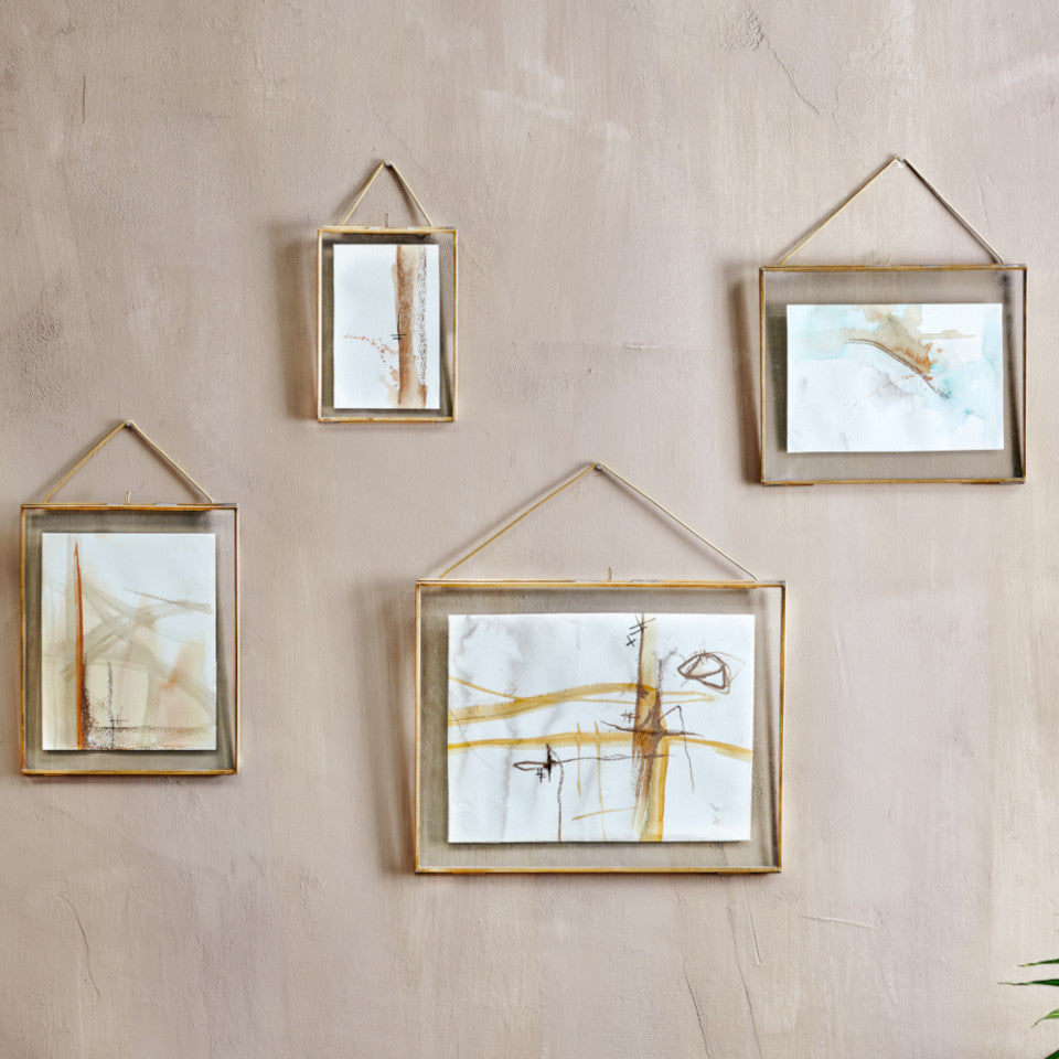 Sambas Kiko brass portrait and landscape frames with brass hanger, styled containing abstract paintings, on a blush painted wall.