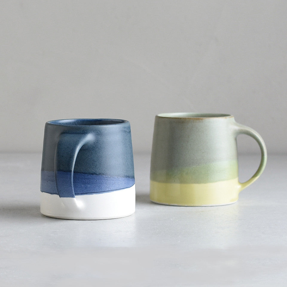 SCS (Slow Coffee Style) S03 mugs, l-r: navy / white and moss green / yellow porcelain coffee mug.