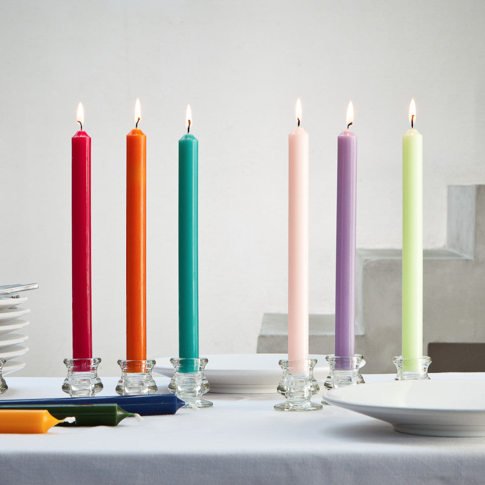 6 small glass candleholders with single dinner candles in different colours styled on a dining table with tableware and 3 candles lying on the table.