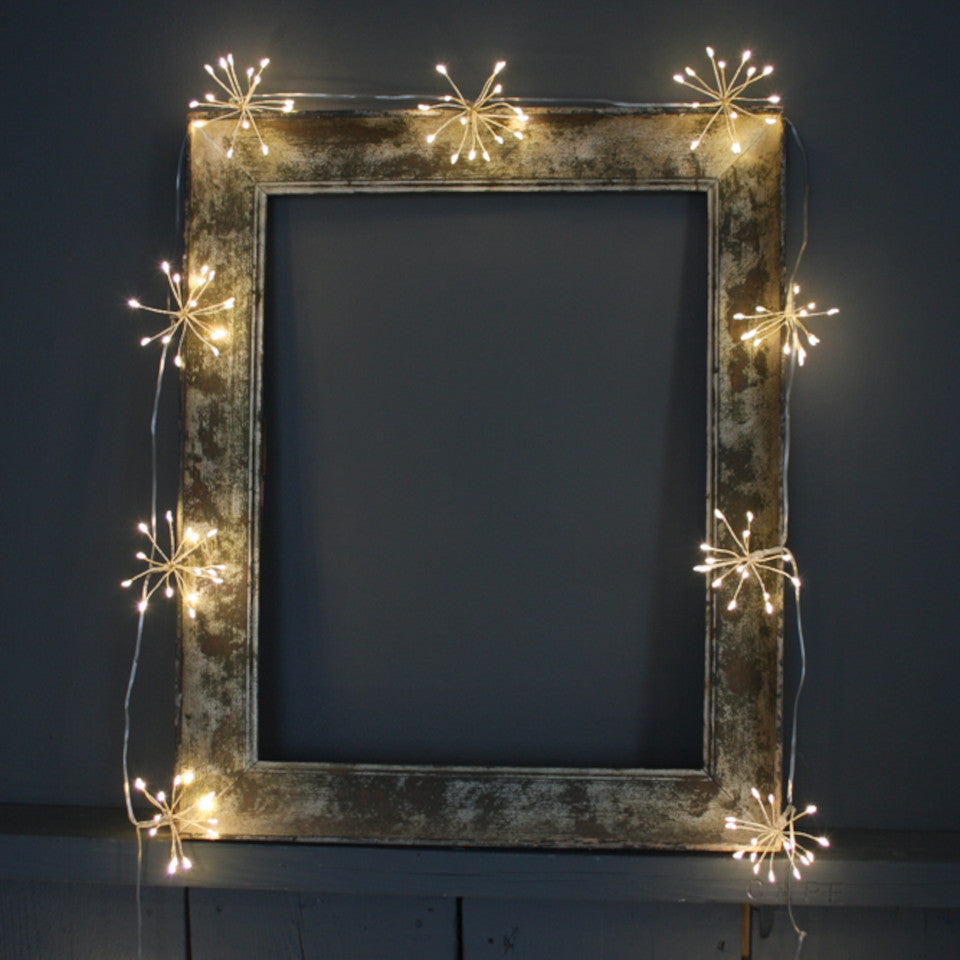 Starburst silver light chain styled draped around a vintage photo frame.