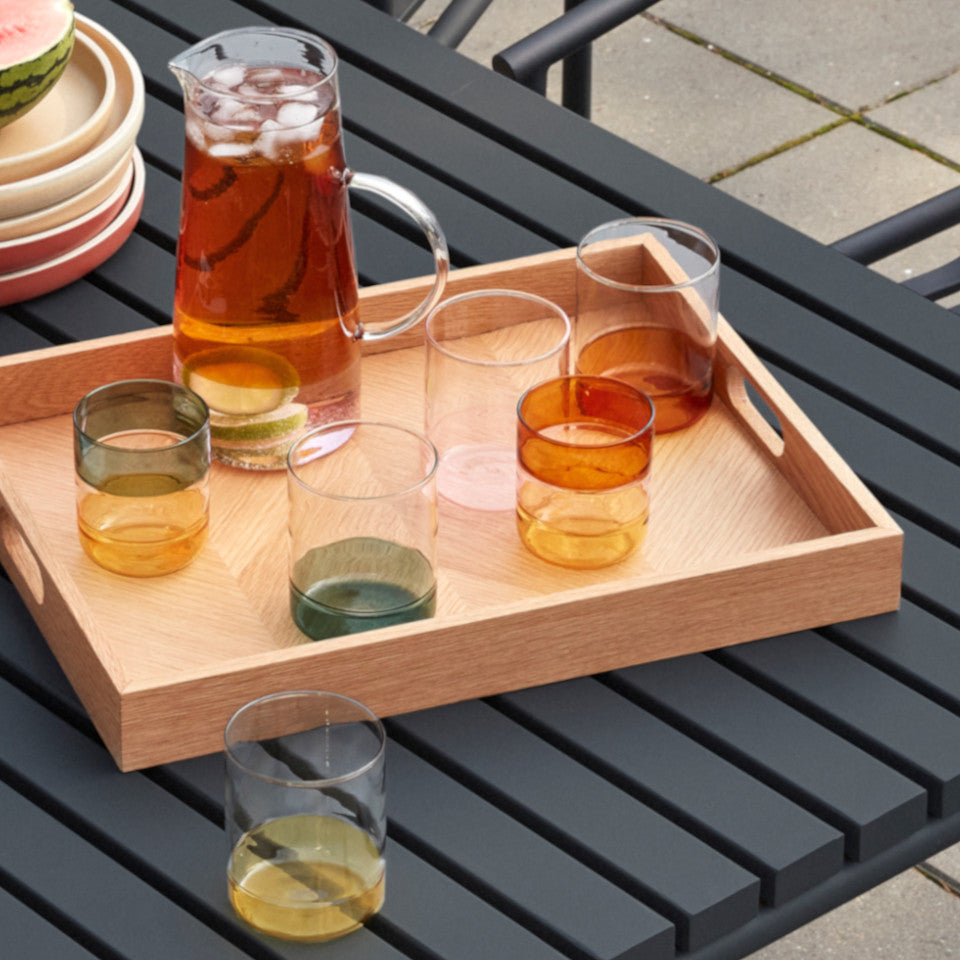 Stripe amber / pink glass jug styled with Stripe set of 2 glasses and Coloured Base set of 4 glasses, on a tray, on an outdoor dining table.