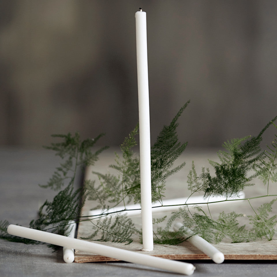 Off-white 30 cm taper candles styled with a fern leaf and candle plate.