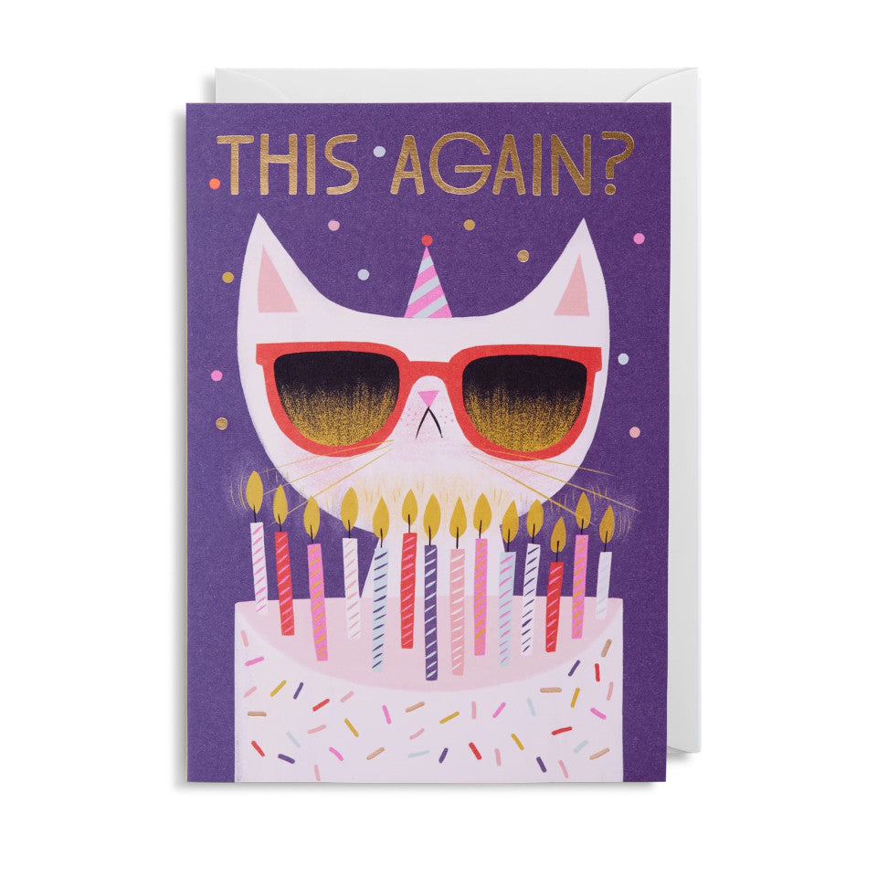 Grumpy Cat This Again?, blank greeting card, with white grumpy cat behind a birthday cake with birthday candles, on a navy background, with white envelope.