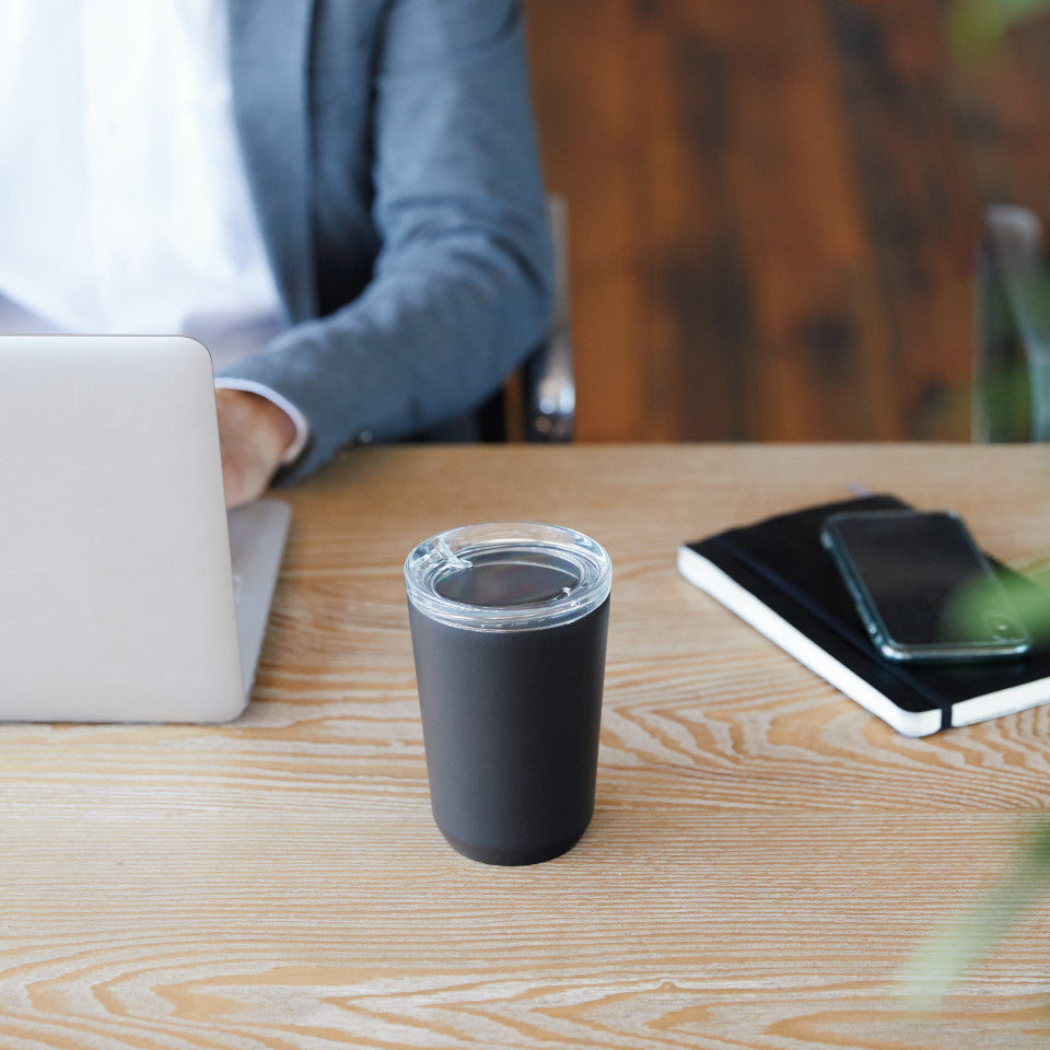 To Go tumbler, black, styled on desk.