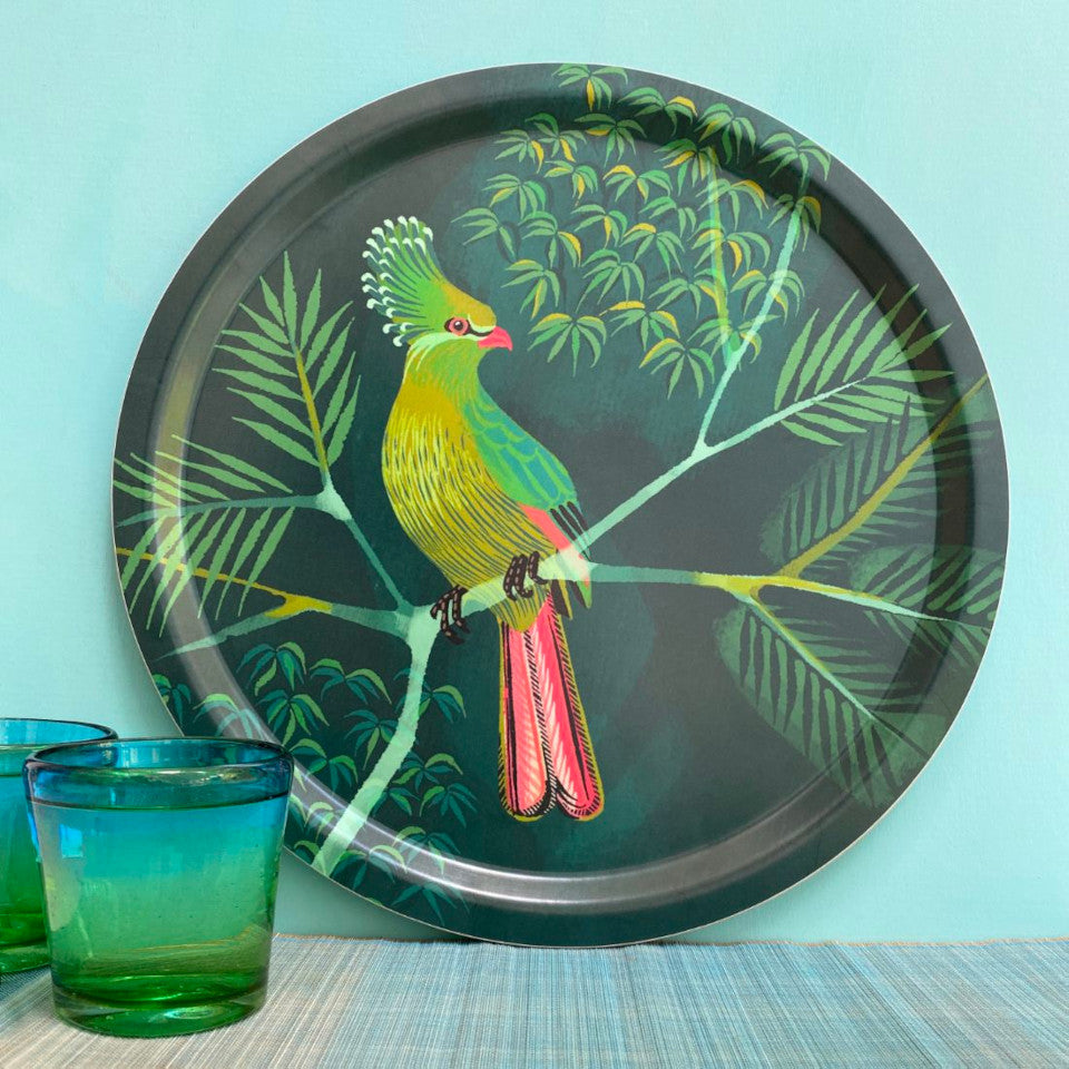 Turaco by Asta Barrington, turaco on tropical tree branch on green background, 39cm round tray, styled leaning against a mint green painted wall, with two green-blue drinking glasses.