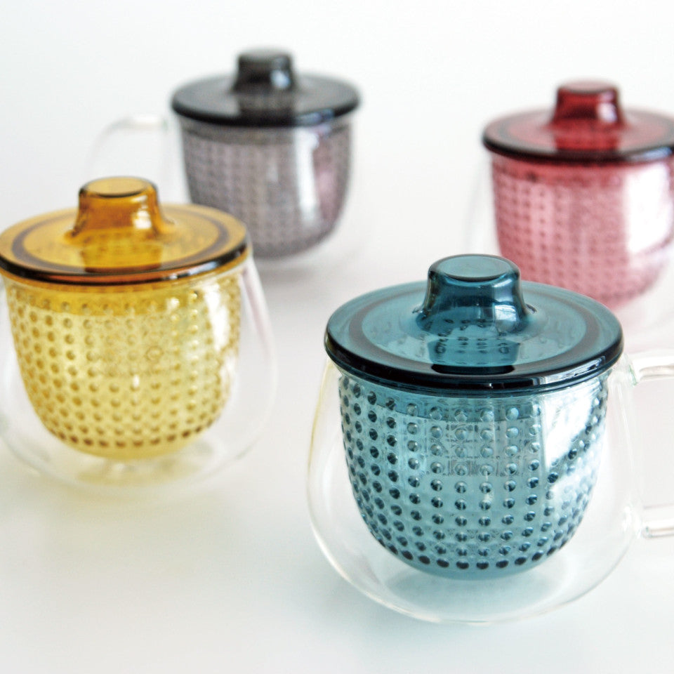Unimug glass mugs with, l-r, yellow, grey, navy and red strainers and lids, styled