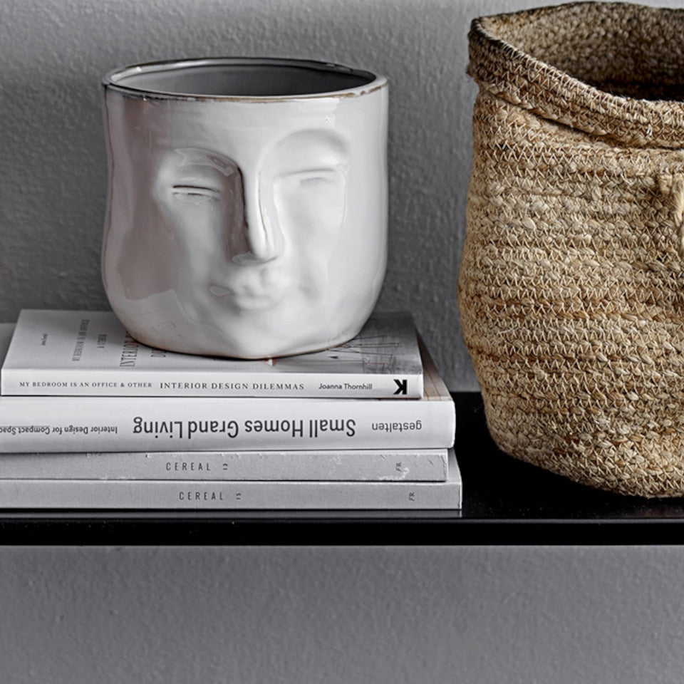 Visage white stoneware 'face' flowerpot, styled on books on a shelf with a storage basket.