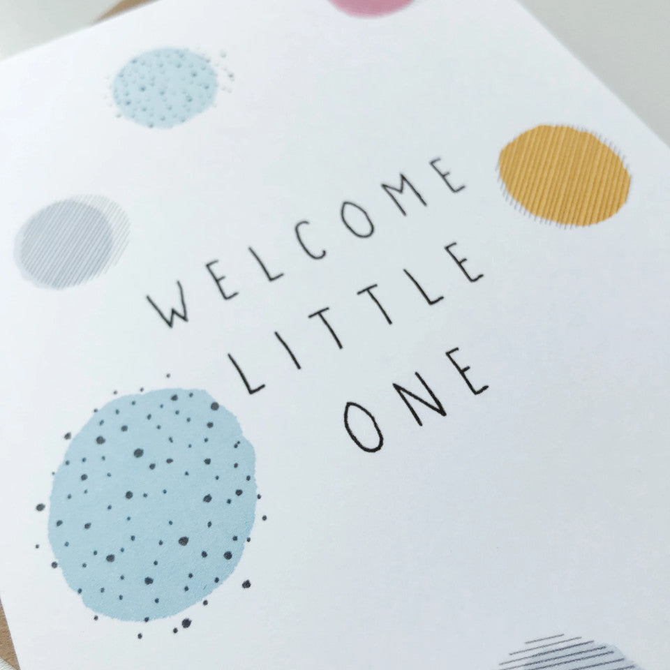 Welcome Little One new baby card, pastel colours spots with black lines, dots and text, close-up.