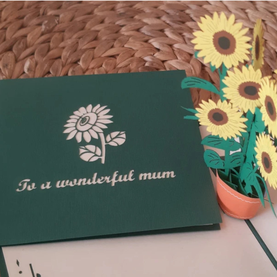 To A Wonderful Mum pop-up sunflower blank dark green Mother's Day card styled on a water-hyacinth stool.