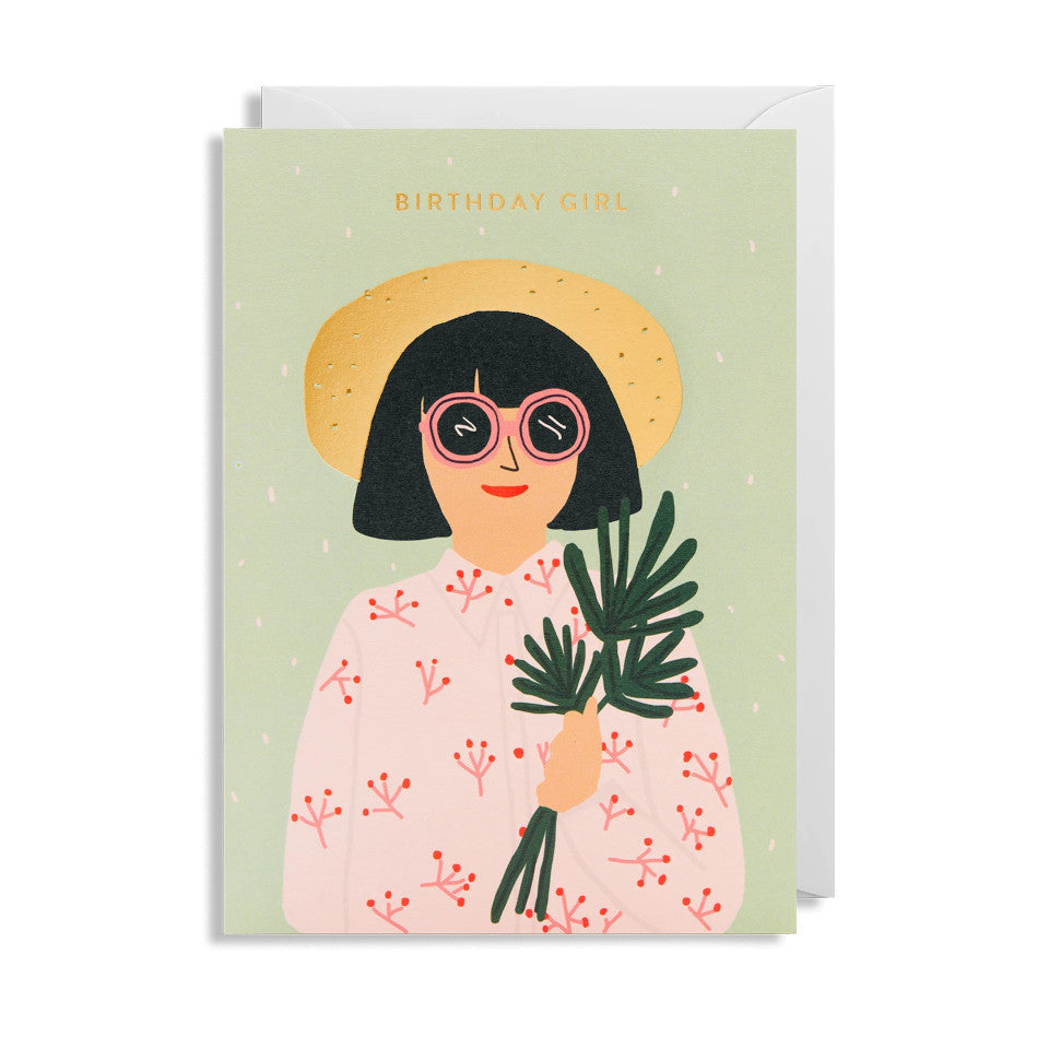 Birthday Girl, Jennifer Bouron designed blank birthday card, with a woman in a sunhat, holding tropical leaves, on a pale green background, with white envelope.