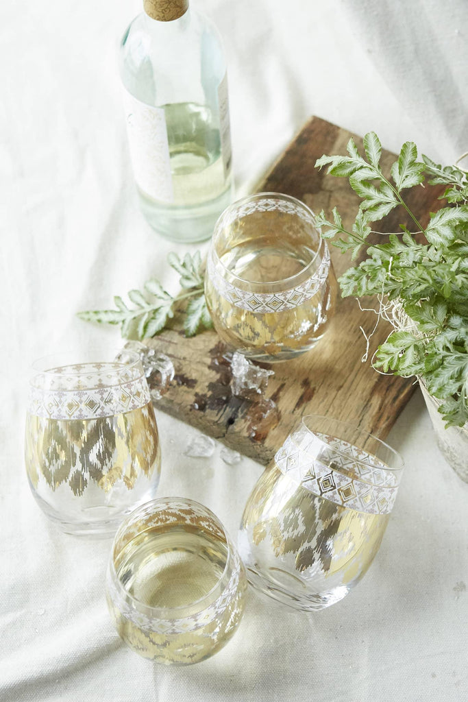 Patina Vie White Twist Stemless Wine Glass on table with wood board and wine botltle
