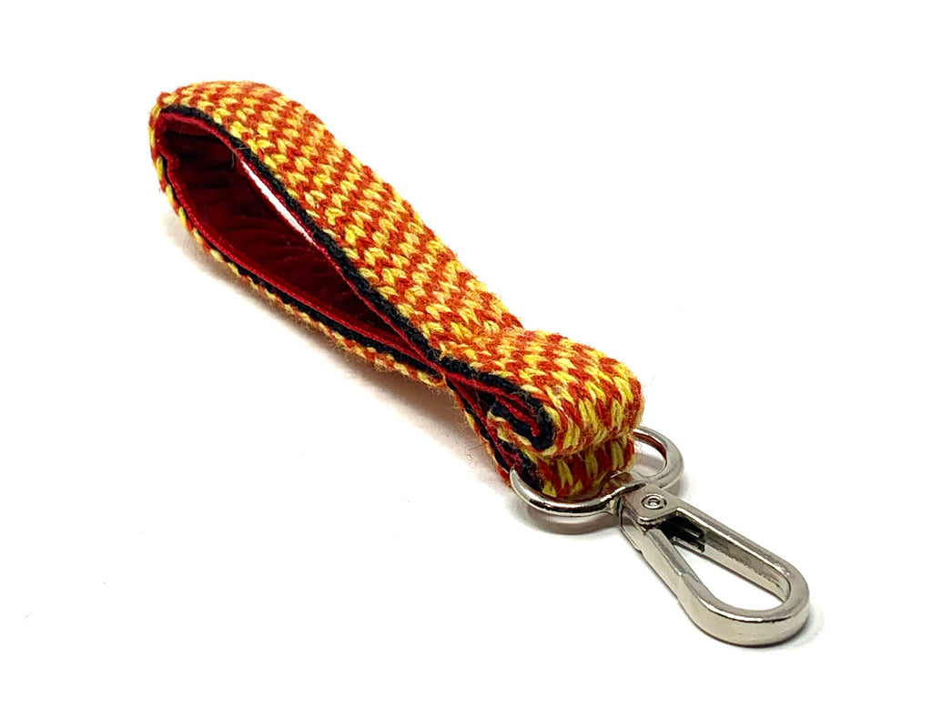 Yellow & Red knitted fabric keyring with a red velvet lining within. The keyring has a silver metal clasp and is placed on a white background.