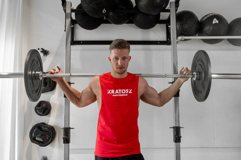 Man in rood sleeveless shirt in de gym met barbell