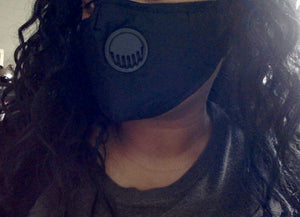 Adjustable black thick fabric face mask with two filters.