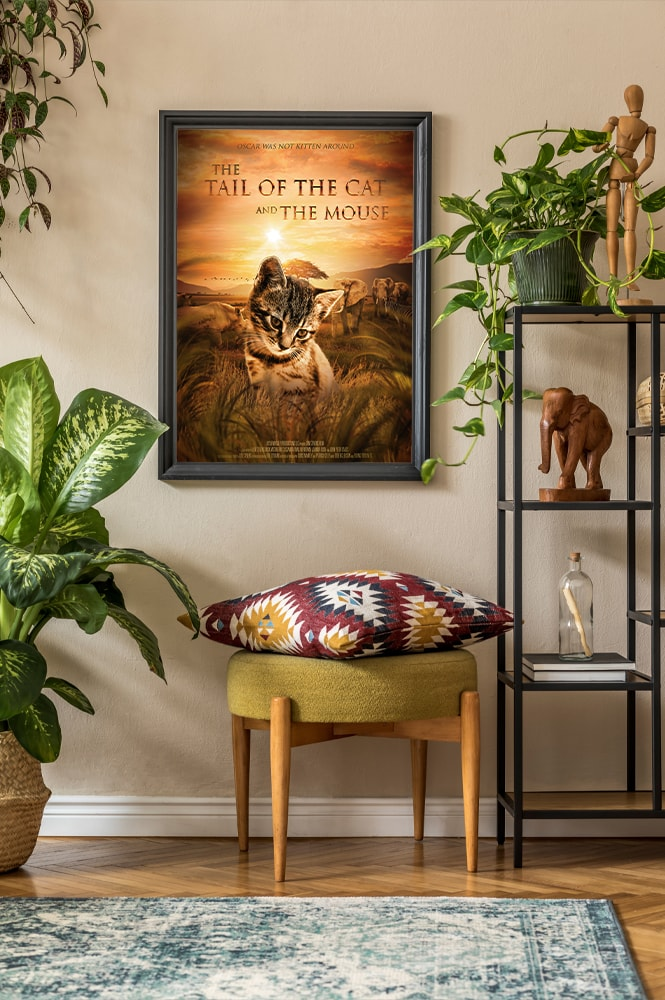 A room with a lot of plants and a movie poster of a cat inside a black frame