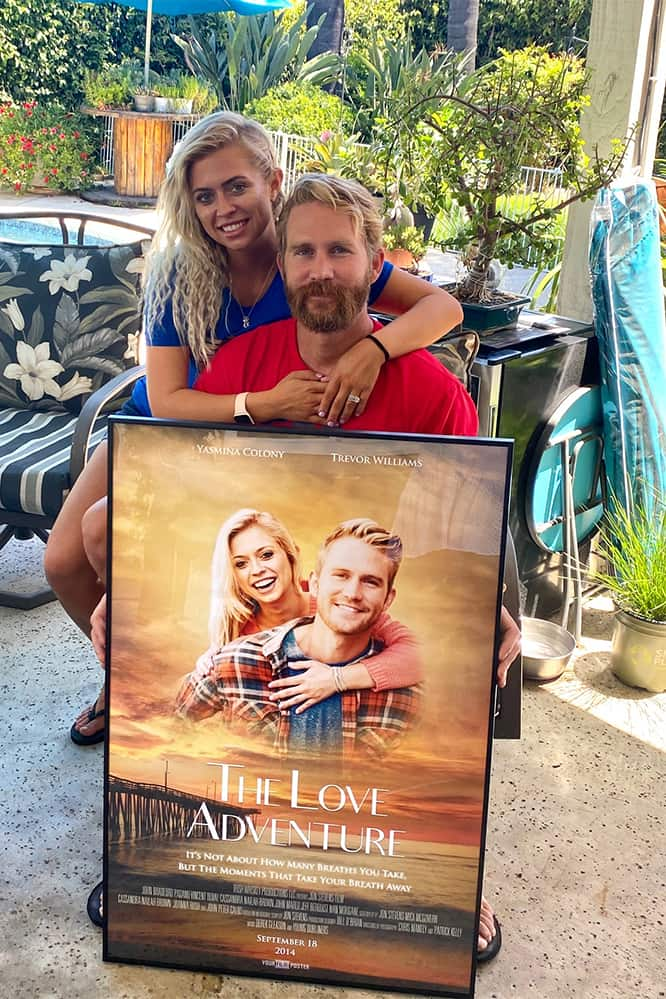 A couple in love showing their own personalized movie poster with their own photo on it as a romantic gift