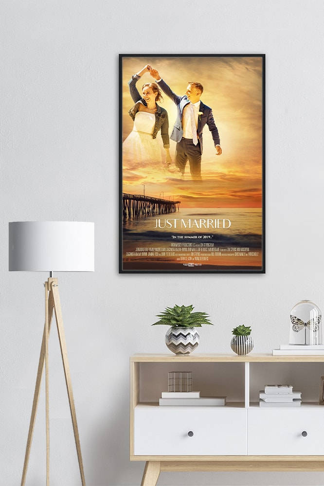 A part of a living room showing a cabinet, lamp and a personalized movie poster in a big black frame on the wall.