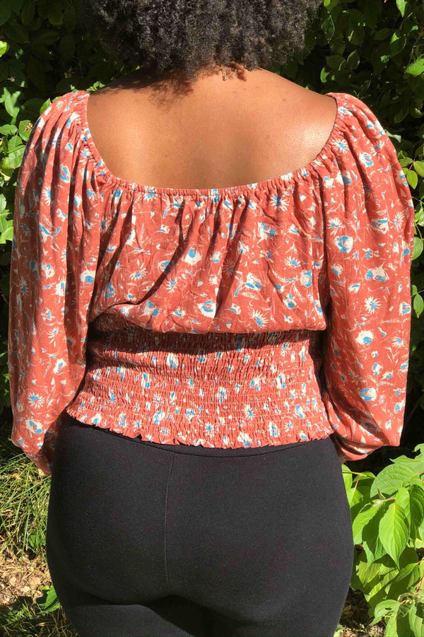 Front tie, long sleeve floral top with smocking detail.