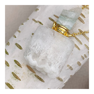 essential oil vial. a beautiful white geode crystal with a geode top. on a gold plated chain. a gorgeous pendant.