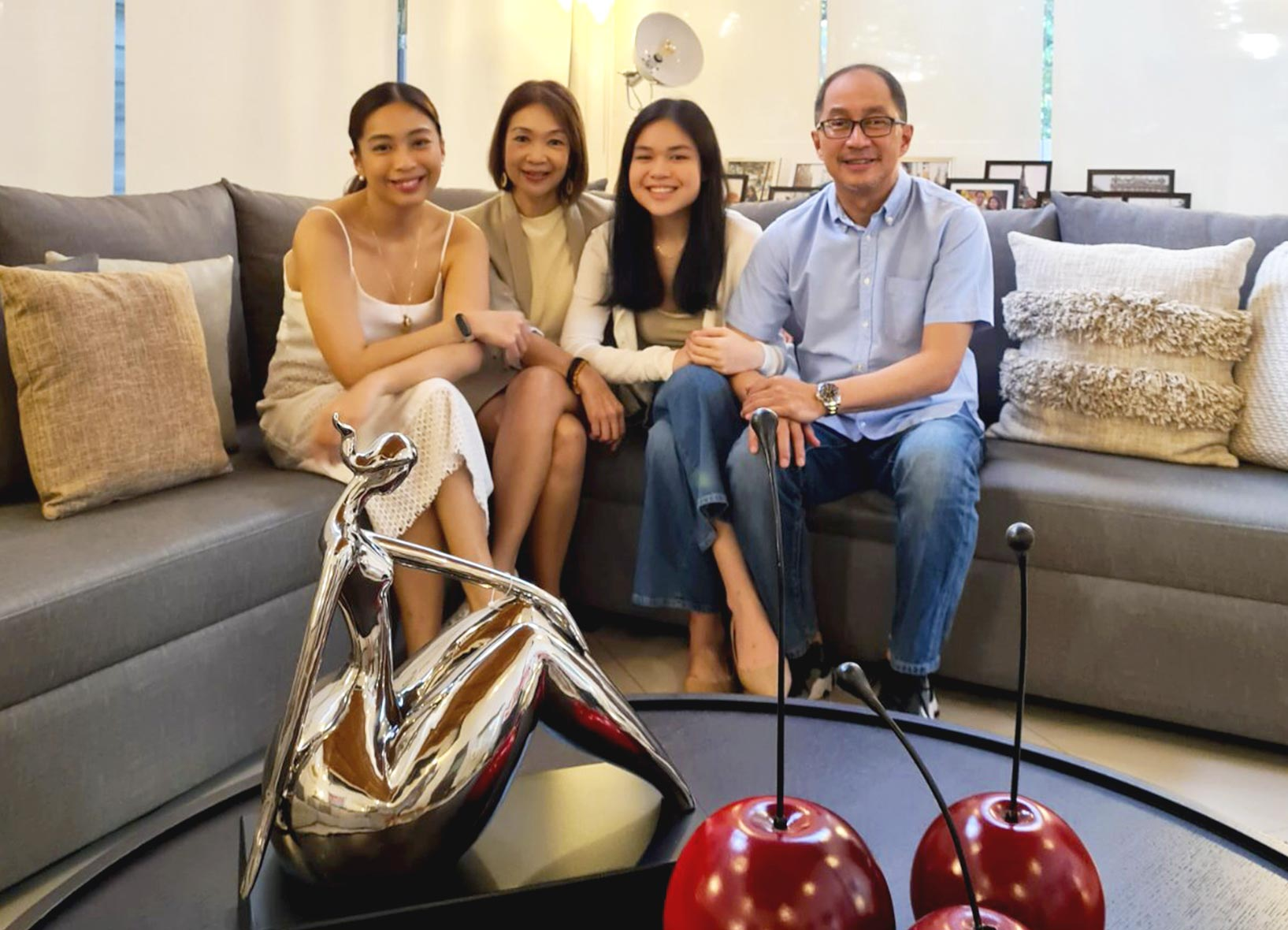 01-Mother_and_father_with_their_two_daughters_sitting_comfortably_on_a_sofa
