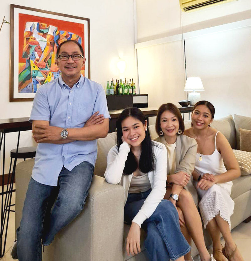 03-Father_leaning_against_a_sofa_with_his_wife_and_daughters_sitting_beside_him