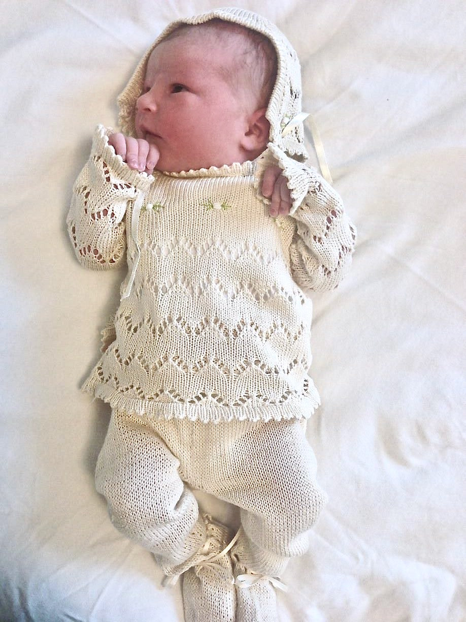Baby with Heirloom knitted romper passed from generations