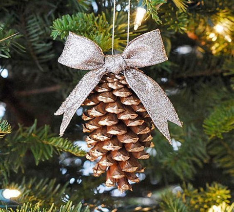 Pine cone dipped in glitter with a bow tied at the top, hanging on a Christmas tree.