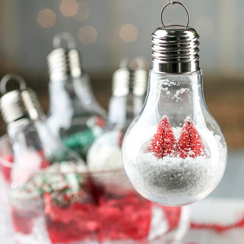 Light bulb christmas decoration filled with fake snow and red Christmas trees.