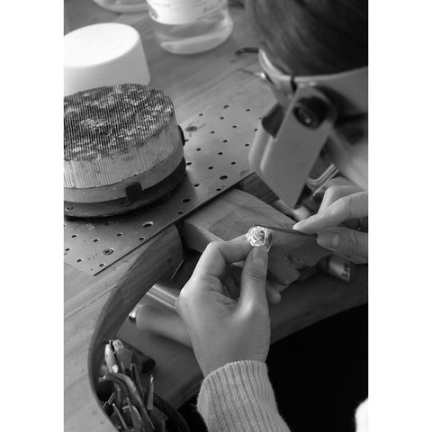 Close up of MJ carving a silver daisy pendant.