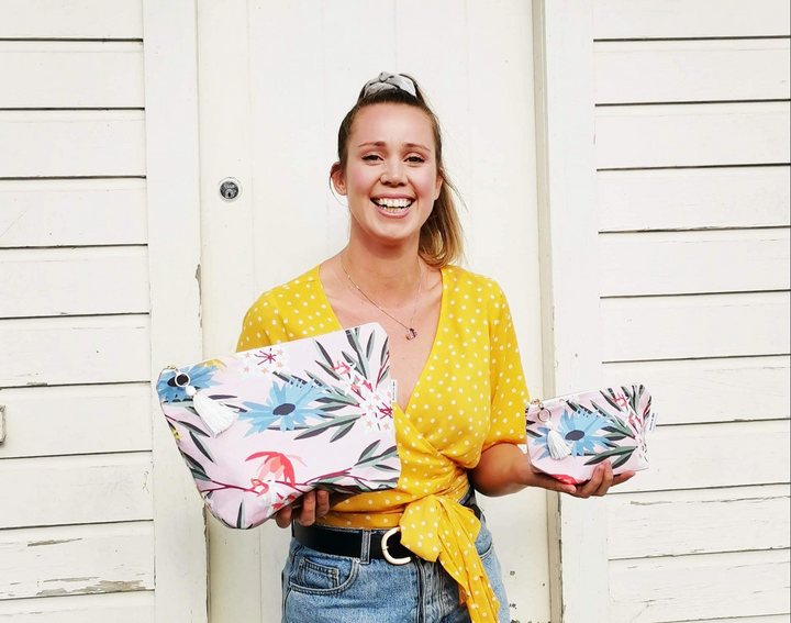 Katie from Sunshine by Katie, holding up her New Zealand made Blossom Makeup & Toiletry Bag