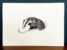 Load image into Gallery viewer, Badger giclée print in black frame on wooden surface. Navy blue wall behind.
