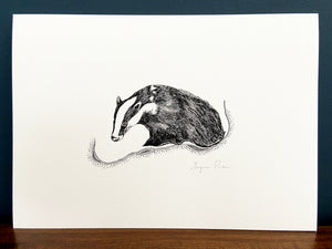Badger giclée print in black frame on wooden surface. Navy blue wall behind.