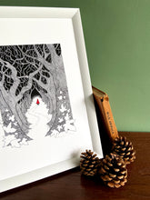 Load image into Gallery viewer, Red Riding Hood giclée print with handpainted watercolour detail in red. Print is in white frame, standing on wooden surface with green wall behind. Pine cones anad book of wild animals stands beside.