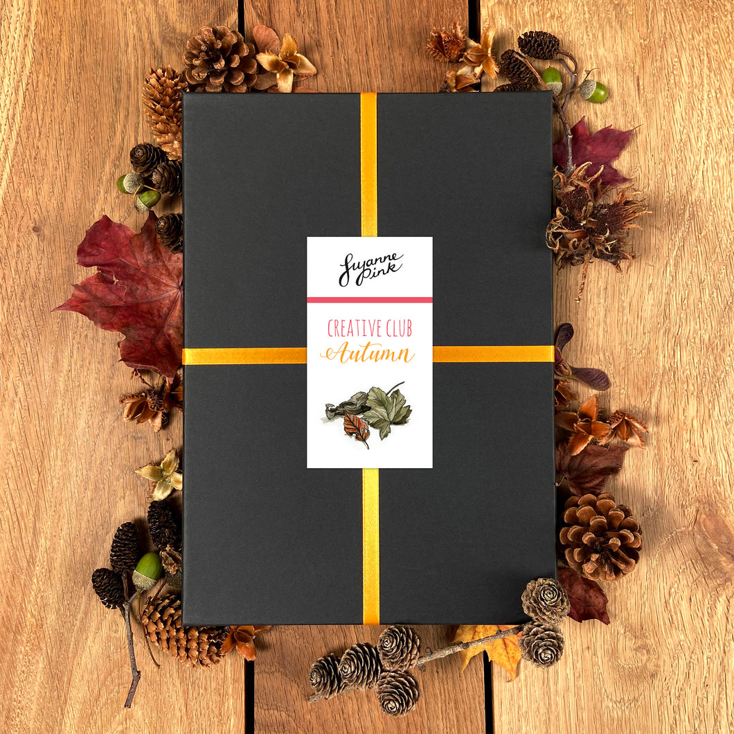 Black presentation box with autumnal design, surrounded by natural autumnal objects.