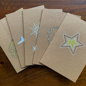 Five kraft greetings cards with handdrawn designs.