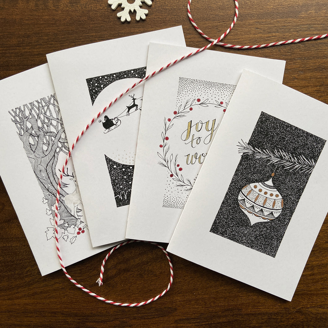 Christmas cards with fineliner illustrations and handpainted details on a wooden background.