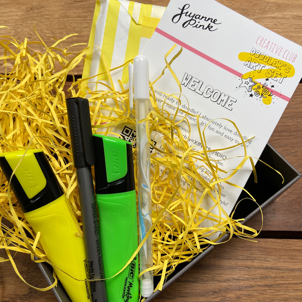 Doodler's Art Set with yellow and green highlighters, white gel pen and fineliner nestled in yellow recycled shredded paper.